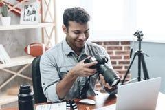 从家的印地安愉快的年轻人摄影师工作 免版税库存图片