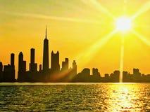 从密歇根湖看的芝加哥地平线,当日落和光束延伸在都市风景在夏天期间 免版税图库摄影