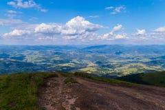 从导致在用绿色盖的小山之间的一个谷的山的一条路在一多云天 库存照片