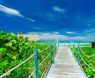 从导致白色沙子海滩和平静的绿松石海洋的木桥的看法在晴天 库存图片