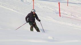 从小山的隐蔽地被采取的滑雪的人 库存图片
