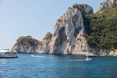 从小船在小船有游人的和卡普里岛海岛峭壁海岸的看法  免版税库存图片