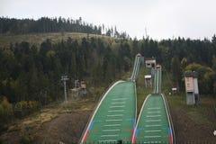 从山的下降到滑雪胜地在夏天用绿草报道 免版税库存照片