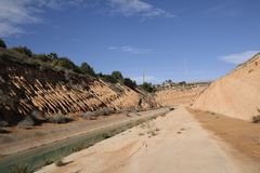 从岩石山坡的Aquaduct出口 库存图片