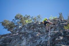 从岩石的Abseiling 人来自下来峰顶 库存照片