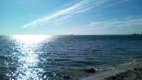 从岸的海视图在一好日子 有轻的波纹的风平浪静水的表面,太阳强光,与轻的分类的天空蔚蓝上 免版税库存图片