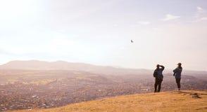 从峭壁边缘的夫妇观看的鸟 库存图片