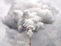 从工厂管子的烟反对阴暗天空 库存照片