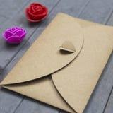 从工艺纸的信封与对此的心脏和在木背景的三朵小的玫瑰花 免版税库存图片