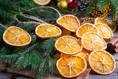 从干桔子、桂香和茴香的圣诞树在木土气桌和杉树上担任主角在背景中 免版税库存图片