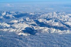 从平面窗口的美丽的cloudscape和雪山 库存照片