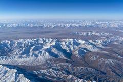 从平面窗口的美丽的cloudscape和雪山 图库摄影