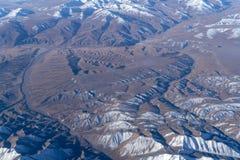 从平面窗口的美丽的cloudscape和雪山 免版税图库摄影