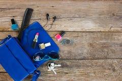 从开放夫人钱包的事 化妆用品和妇女` s辅助部件落在蓝色提包外面 库存照片