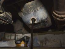 从引擎排泄老油通过放油塞 免版税库存图片