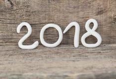 从形成第2018年,元素的白色黏土的数字在土气木背景的一个明信片新年2018年 库存图片