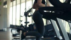 从快速地跑在健身俱乐部的轨道踏车的belowof健身女孩的英尺长度 运动服工作的白肤金发的女孩 影视素材