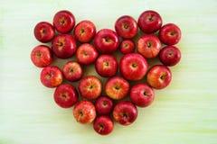 从成熟红色苹果的心脏在绿色木背景 免版税库存照片
