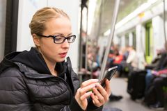 从手机屏幕的女孩读书在地铁 免版税图库摄影