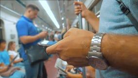 从手机智能手机屏幕的偶然人读书,当神色旅行在地铁时的地铁的导航员 慢 股票视频