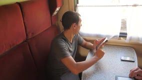 从手机生活方式屏幕一会儿的偶然人读书在火车无盖货车读移动sms的消息 慢的行动 股票录像