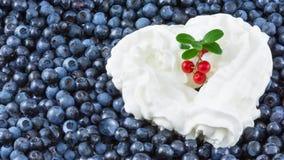 从打好的奶油的白色心脏在蓝莓背景 库存图片