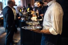 从承办酒席服务运载的香槟酒的侍者在事件喝 免版税库存图片