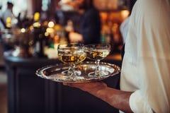 从承办酒席服务运载的香槟酒的侍者在盘子喝在事件 库存照片