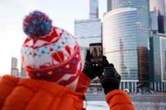 从拍摄在智能手机的人后面的照片大厦 免版税库存图片
