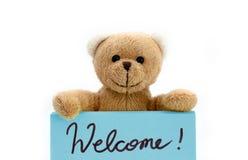 从拿着用两只手在蓝色颜色的棕色玩具熊的欢迎消息笔记与手写的消息 免版税图库摄影