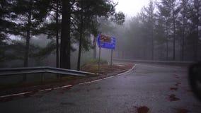 从接近对沿路旁的交叉点的汽车的美丽如画的看法在森林附近在雨以后 E ? 股票录像