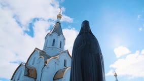 从教士古铜色或石雕象底部的看法在东正教附近的在反对蓝色多云天空的好日子 影视素材