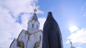 从教士古铜色或石雕象底部的看法在东正教附近的在反对蓝色多云天空的好日子 股票视频