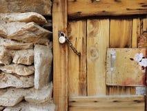 从新的棕色自然委员会的木门毗邻古老石墙,被修筑冰砾,并且是闭合的在挂锁机智 免版税图库摄影