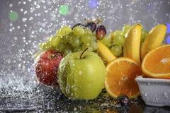 从新鲜的五颜六色的果子的欢乐静物画在下落和飞溅落的水 免版税库存照片
