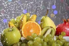 从新鲜的五颜六色的果子的欢乐静物画在下落和飞溅落的水 库存图片