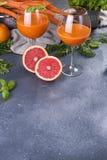 从新鲜的红萝卜和葡萄柚在玻璃,健康饮食的维生素饮料的汁液 在食物的维生素 复制空间 图库摄影
