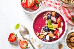 从新鲜的莓果、坚果和格兰诺拉麦片的圆滑的人碗 库存照片