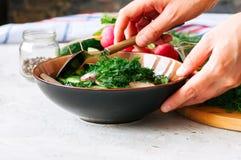 从新鲜蔬菜的健康沙拉在做 妇女的手混合 免版税库存照片