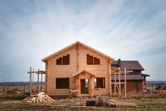从日志建造的新的木房子,在蓝天背景的未完成的生态木大厦 图库摄影