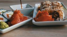从日本烹调的鲜美美好的大白色和黑寿司卷在桌上的盛肉盘站立在餐馆 影视素材
