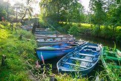 从早晨太阳的透镜火光通过树和横跨小船栓了对运河的边 库存照片