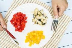 从有机菜的素食沙拉在白色板材 切好的甜椒和茄子 妇女手举行刀子和叉子 脊椎 库存图片