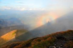 从有橙色草的草坪打开高山、蓝天与云彩和一个布罗肯峰幽灵全景在雾 免版税图库摄影