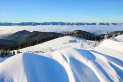 从有织地不很细随风飘飞的雪的草坪有看法对冬天风景,在雪的公平的树,老小屋,高山,雾 库存图片