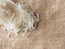 从有脚的小玻璃的白色未加工的米下落在棕色麻袋布背景 库存照片