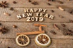 从木信件和数字'新年快乐'一辆自行车和一棵树的题字从香料在粗砺的木头背景  库存图片