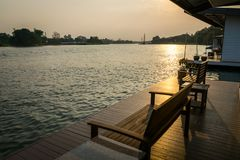 从木筏房子的河侧视图日落时间的 图库摄影