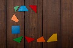 从木逻辑比赛的色的部分的未完成的框架在木棕色桌上的 复制空间 库存图片