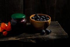 从李子和李子莓果的自创果酱在一个木碗 免版税库存照片